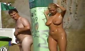 Voluptuous blonde Milf showers on the beach