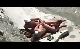 Mature couple caught spooning at the beach